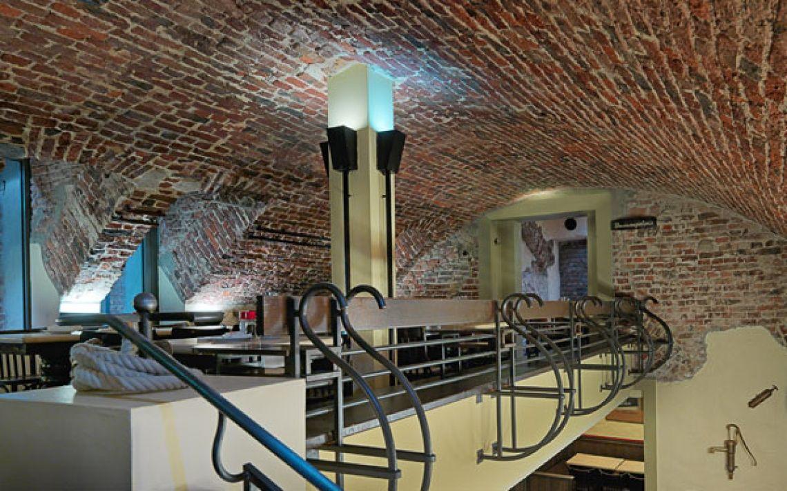 """Das Brauhaus FRÜH am Dom, Brunnengalerie und Gewölbekeller Brunnengalerie und Gewölbekeller Ein weiteres Highlight in unserem Brauhauskeller ist die """"Brunnengalerie"""", die sich auf einer Empore über dem Brunnengewölbe befindet. Der Raum ist durch das Gewölbe der alten Steinmauern geprägt, die eine ganz besondere Atmosphäre schaffen. Die urige und rustikale Stimmung lädt zum Verweilen, plaudern und Kölsch trinken ein. Von den Sitzplätzen auf der Brunnengalerie hat man einen schönen Blick auf das Treiben im Brauhauskeller. Im hinteren Bereich der Galerie befindet sich die Gewölbestube, ein idealer Platz für eine kleine Gruppe bis 8 Personen. Sitzplätze Brunnengalerie: 42"""