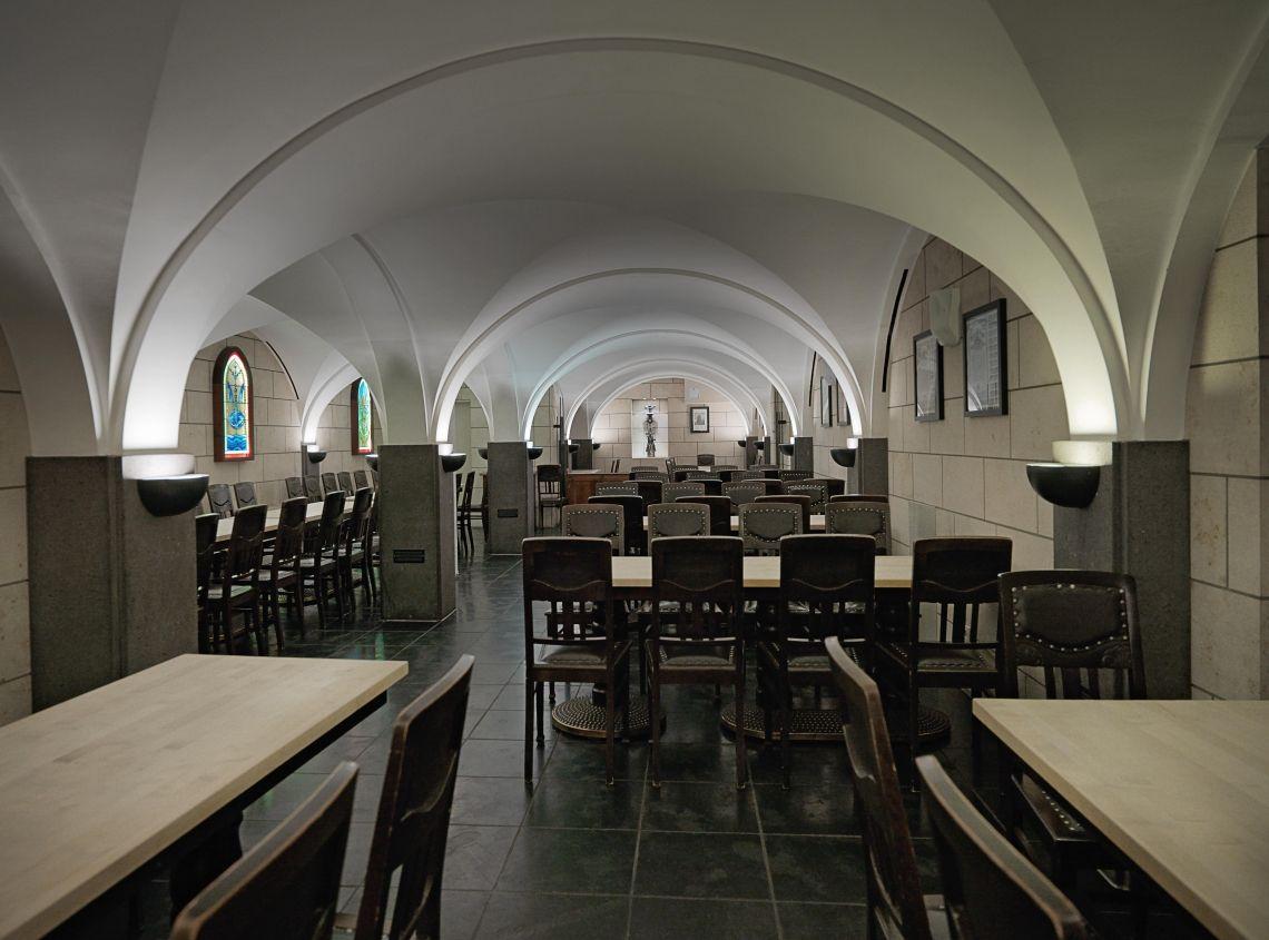 Das Brauhaus FRÜH am Dom, Kapellchen Als Freunde und Förderer des Kölner Doms haben wir unser eigenes Kapellchen. Die Rundbögen, der französische Kirchenboden und die beleuchteten bunten Bleiglasfenster verschaffen dem Raum ein besonders festliches Ambiente. Viele Erinnerungsstücke sind Originale aus dem Kölner Dom, wie die Gebetsbänkchen, die Fialen, Dachreiter, alte Zeichnungen und Stiche. Die Wände bestehen aus dem gleichen Sandstein aus dem Siebengebirge, aus dem auch ein Großteil des Doms gebaut wurde.