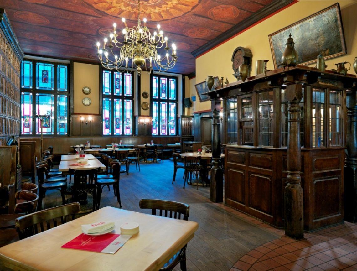"""Das Brauhaus FRÜH am Dom, Restaurant und Schänke Das Hauptrestaurant zeigt den typischen Stil eines traditionellen Kölner Brauhauses. Neben dem klassischen """"Kölner Stuhl"""" (auch Beichtstuhl oder Gebetsstuhl genannt), von wo aus der Geschäftsführer schon 1904 die Geschäfte leitete, findet man hier alte Kachelöfen und Deckenmalerei. Die Speisen und alle alkoholfreien Getränke werden am """"weißen Buffet"""" ausgegeben. In der Schänke zapft der """"Zappes"""" aus 90 Liter Holzfässern das frische Kölsch und bedient die """"Köbesse"""" auf Zuruf, bzw. in dem diese ihre Biermarken oder Bons abgeben. Wer richtig typisch kölsche Brauhaus-Atmosphäre schnuppern will, sollte hier wenigstens 1-2 Kölsch im Stehen in der Schänke trinken."""