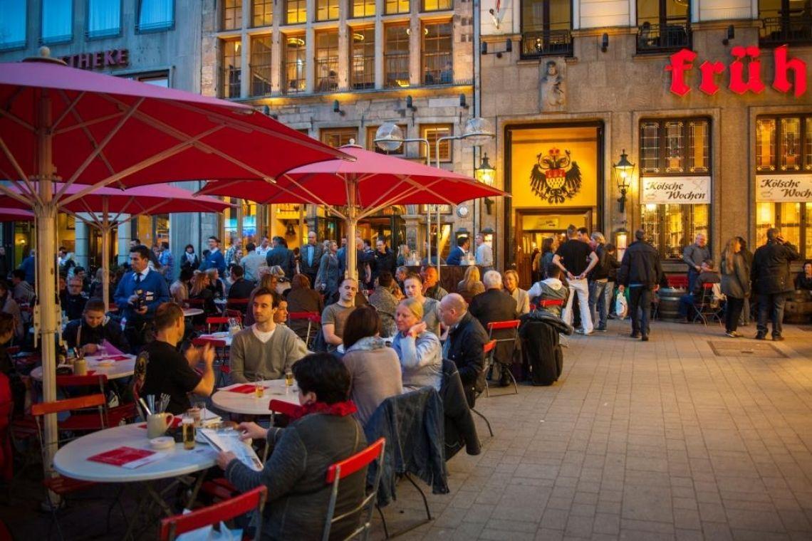 """Der Biergarten direkt vor dem Brauhaus FRÜH am Dom, gleich um die Ecke  Sobald die Temperaturen wärmer werden und die Sonne am Kölner Himmel strahlt, ist der FRÜH Biergarten ein beliebter Treffpunkt für ein schnelles Kölsch nach dem Einkaufsbummel oder einen rheinischen Snack. Vor dem Haupteingang zum Brauhaus FRÜH am Dom kann man hier das bunte Treiben rund um den Dom und den Heinzelmännchenbrunnen aus erster Reihe beobachten. An den Wochenenden kann man schon morgens unser reichhaltiges """"Früh""""-stück genießen. Mittags serviert der Köbes die gleichen kölschen und regionalen Gerichte wie man sie im Brauhaus findet. Mit der stetigen Vergrößerung des Hauses FRÜH hat sich der Biergarten inzwischen über den gesamten Platz von den Häusern Am Hof 12 bis 18 ausgedehnt und bietet 280 Sitzplätze."""