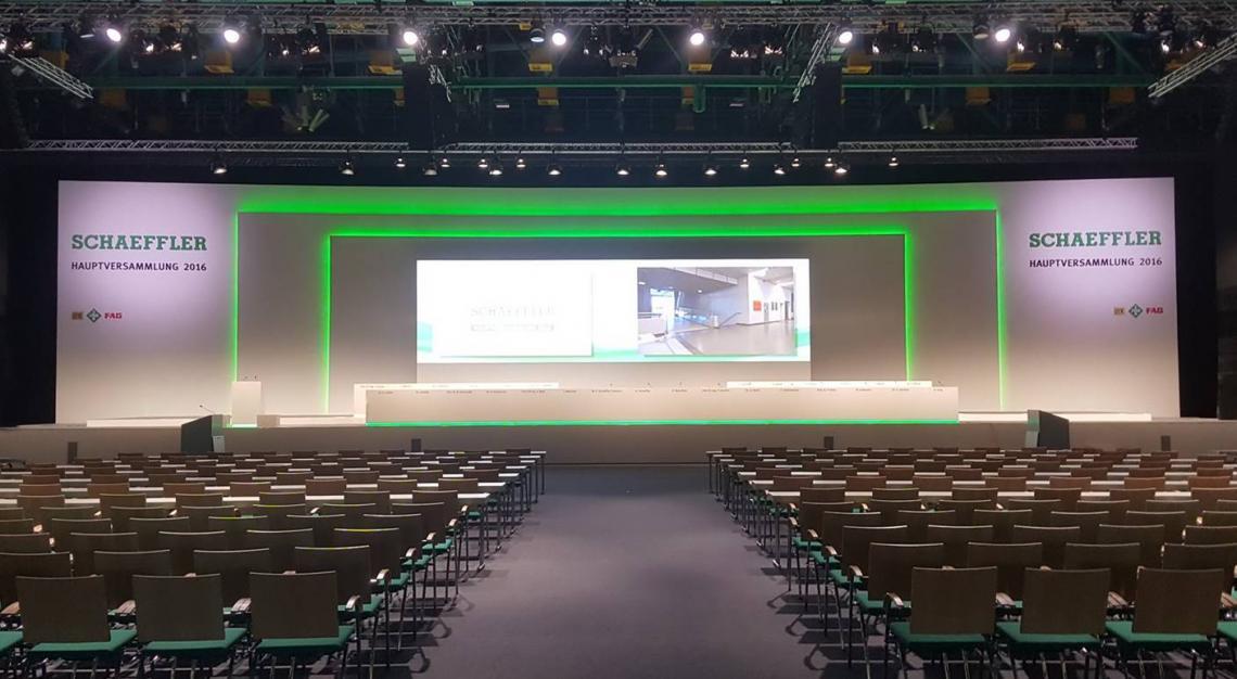 Schaeffler AG Hauptversammlung Die 1. Hauptversammlung der Schaeffler AG fand am 22.04.2016 in Nürnberg statt. DEKO-Service war verantwortlich für das gesamte Bühnenbild und den Bühnenbau. Die Rückwände erhielten eine vollflächige Bespannung mit einem maximal Maß von 37,5 x 9 m. Das Bühnenpodest wurde mit CNC gefrästen Sonderpodesten erstellt.