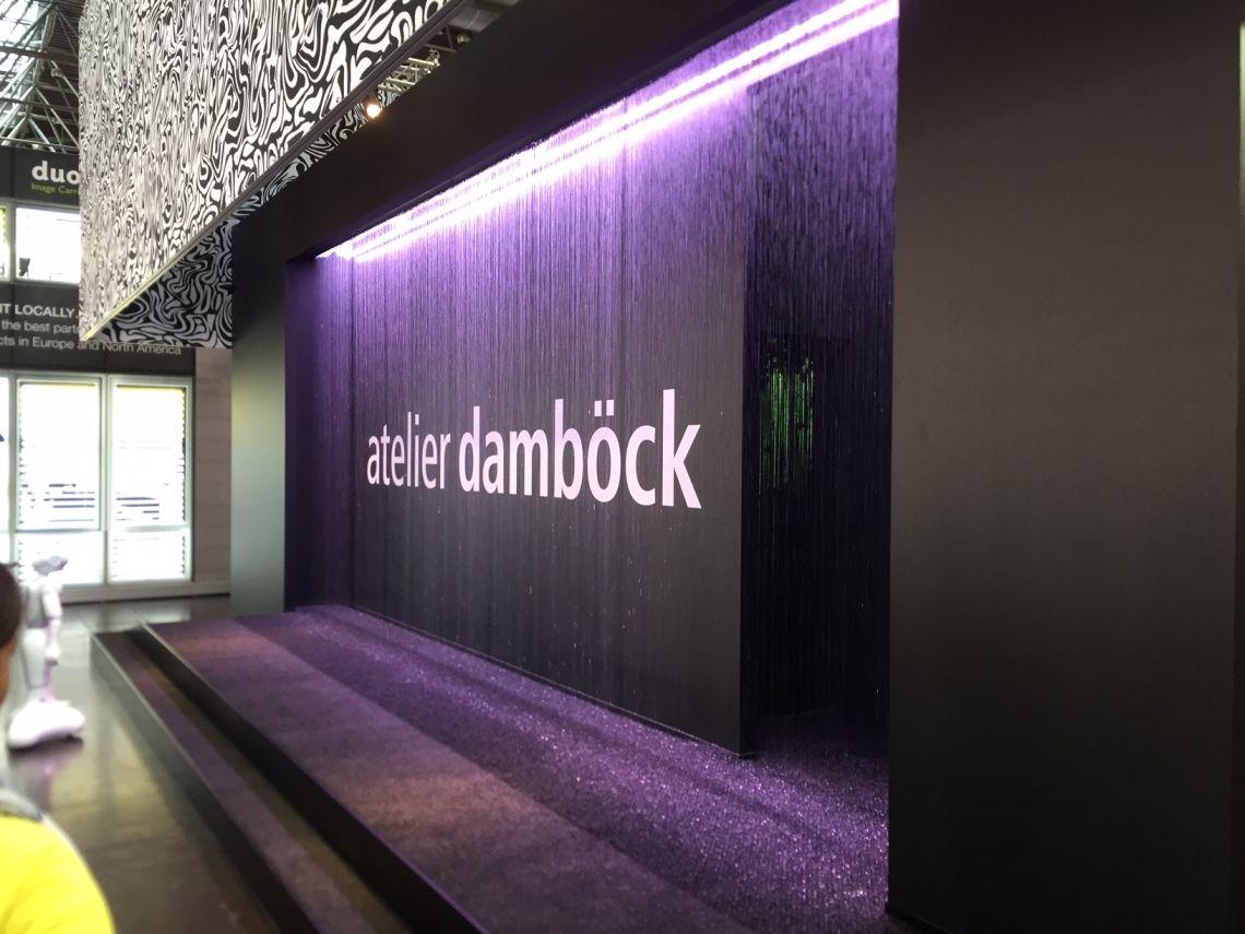 atelier damböck auf der EuroShop 2017 Das Unternehmen Atelier Damböck präsentierte sich dieses Jahr mit einem innovativen und mutigen Konzept auf der Leitmesse EuroShop in Düsseldorf. Eine sieben Meter lange Regeninstallation von as systems war dafür auf dem Stand des Unternehmens Atelier Damböck in Halle 5 im Einsatz.