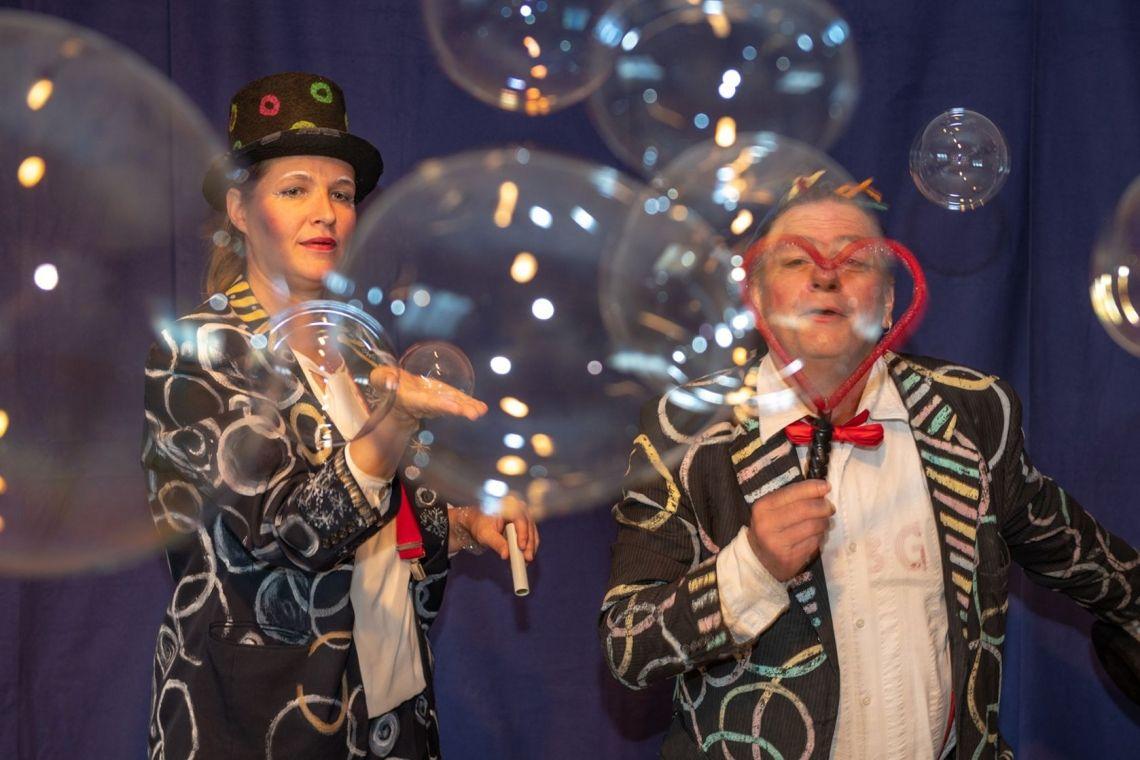 """Seifenblasen Show Ein Zauber für Tag und Nacht ! Seifenblasen scheinen im Dunkel der Nacht eine noch magischere Ausstrahlung zu haben als bei Tageslicht. Anlässe dafür gibt es genug. Ob im Sommer oder Winter, ob """"Flammende Sterne"""", """"Sternschnuppennacht"""", Straßenfest, Kindergeburtstage, lange Einkaufsnächte oder auf sonstigen Lichterfesten. Der WOW-Effekt wird bei Dunkelheit noch größer und die Lichtquellen spiegeln sich tausendfach in den Blasen. Lichtgeschwindigkeit scheint neu erfunden. In wabernden Blasen reisen Licht und Farben langsam durch die Nacht..."""