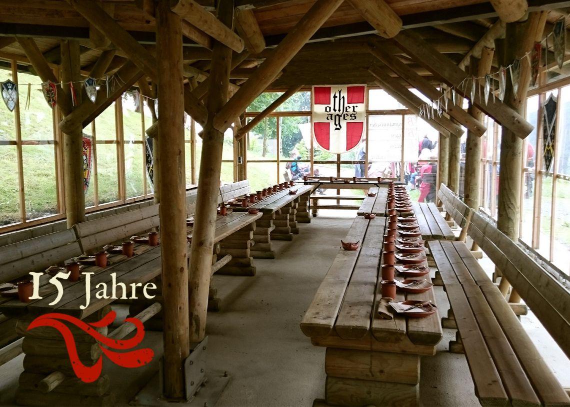 """""""Rittermahl überall"""" Als ziemlich erfolgreiche Idee hat sich """"Rittermahl überall"""" erwiesen. Diese Veranstaltungen finden an wechselnden Orten außerhalb unserer gewohnten Locations statt, indoor oder im Freien. So wird man zum fahrenden Volk! Wir waren z. B. schon in einem privaten Garten mit selbstgebauten (!) Tischen und Bänken aus Baumstämmen, oder haben eine Parzelle auf einem Mittelaltermarkt genutzt, wo das Ambiente natürlich von alleine passt. Auch sehr schön: Auf dem Bild sind wir 2016 zu Gast in der Grillhütte des RAG Haus Niederberg."""