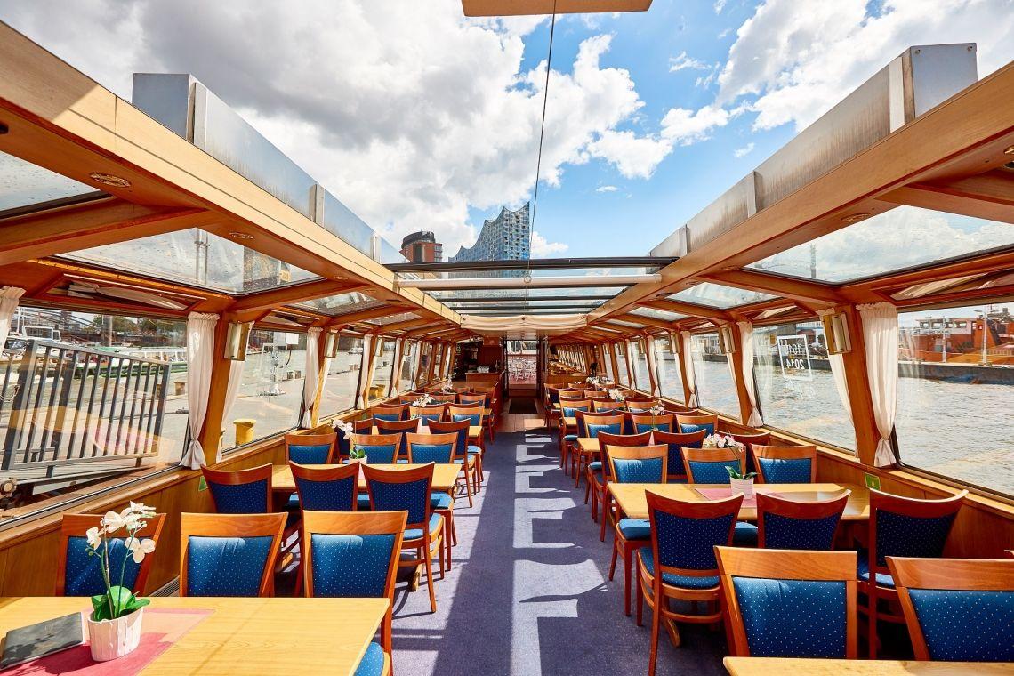 Hamburger Deern Innenansicht Unser Fahrgastschiff mit dem großen Schiebedach lässt Sonne und Fahrtwind in den Fahrgastraum, während man gemütlich an Tischen bedient wird.