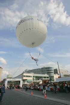 """Art Ballooning Schwerelosigkeit und Anmut sind die Attribute dieser exklusiven Animation. Engelsgleich fliegt die Künstlerin über die Köpfe der Zuschauer, gleitet durch die Luft dem Publikum entgegen, berührungsnah, um gleich wieder zu entschweben. Von einem Heliumballon sanft getragen, dreht und wirbelt die Tänzerin beliebig durch den Luftraum und zieht eine Spur von Glitterstaub hinter sich her.  Auf Wunsch können auch Werbegeschenke aus der Luft verteilt werden. Der Ballon kann von innen beleuchtet werden oder dient als Projektionsfläche für Gobos, Videos, etc. oder als beliebiger Hängepunkt im Raum für unsere Nummer """"Aerial-Silk""""."""