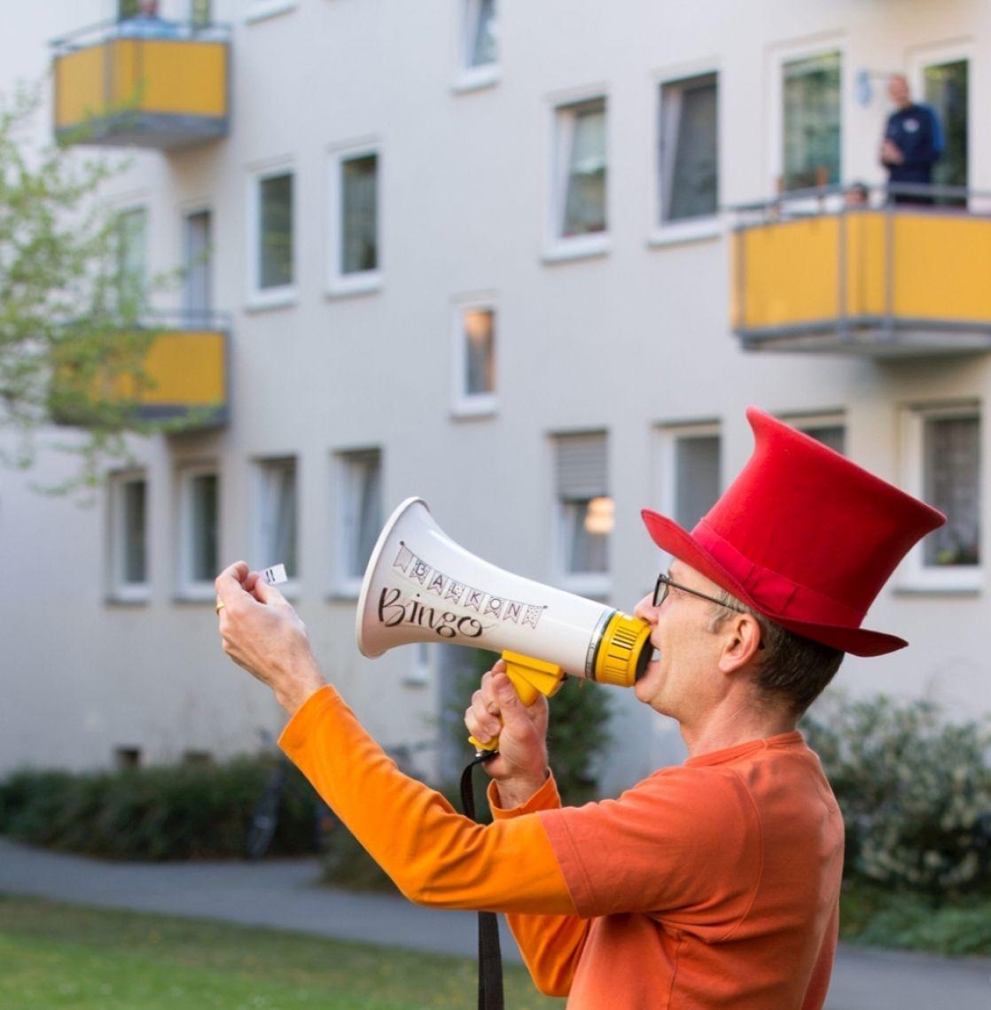 """Corona-Sonderprogramme: Hofbespielung mit Balkon-Bingo Der Moderator auf Stelzen, als solcher schon eine Attraktion, leitet durch die mitreißende Show. Er begrüßt die Nachbarn auf den Balkonen oder Fenstern. Nach und nach zieht der Moderator die Gewinnzahlen und animiert die Zuschauer zu Ja- und Jubelrufen bis der Gewinner """"Balkon-Bingo"""" ruft. Er wird gefeiert und erhält ein symbolisches Geschenk. Nach """"Zugabe""""-Rufen wird sogar noch ein zweiter Gewinner* ausgespielt."""