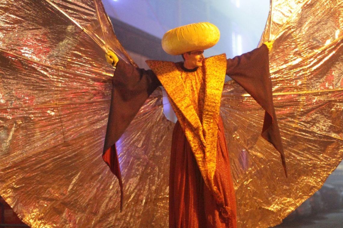 """Corona-Sonderprogramme: Stelzenprogramm Mond und Werwolf Tanz und Performance auf Stelzen zur Musik. Eine ästhetische Intervention zum Träumen und Staunen. Durch seine ungewöhnliche Größe sehr gut zu sehen.  Eine ungewöhnliche Gesellschaft. Unübersehbar. Rätselhaft. Der """"Mond"""" als Phantasiewesen verzaubert sein Publikum mit fließenden Formen und Bewegungen. Der """"Werwolf"""" dagegen versteckt sich, schleicht herum oder sucht Unterschlupf beim Mond, dann wieder springt er verspielt und kraftvoll herum."""