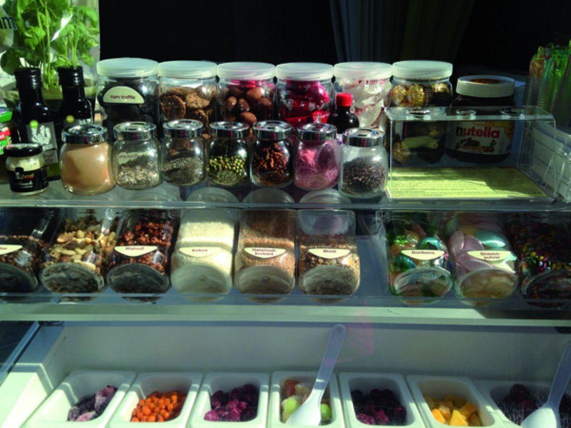 EiZbar-Auslage Sie sehen unten die Früchte, darüber die Süssigkeiten, Müsli, Nüsse, Kaffee und oben verschiedene Spezialitäten von Chili über Knoblauch und Meerrettich sowie Basilikum und hochwertige Genussartikel