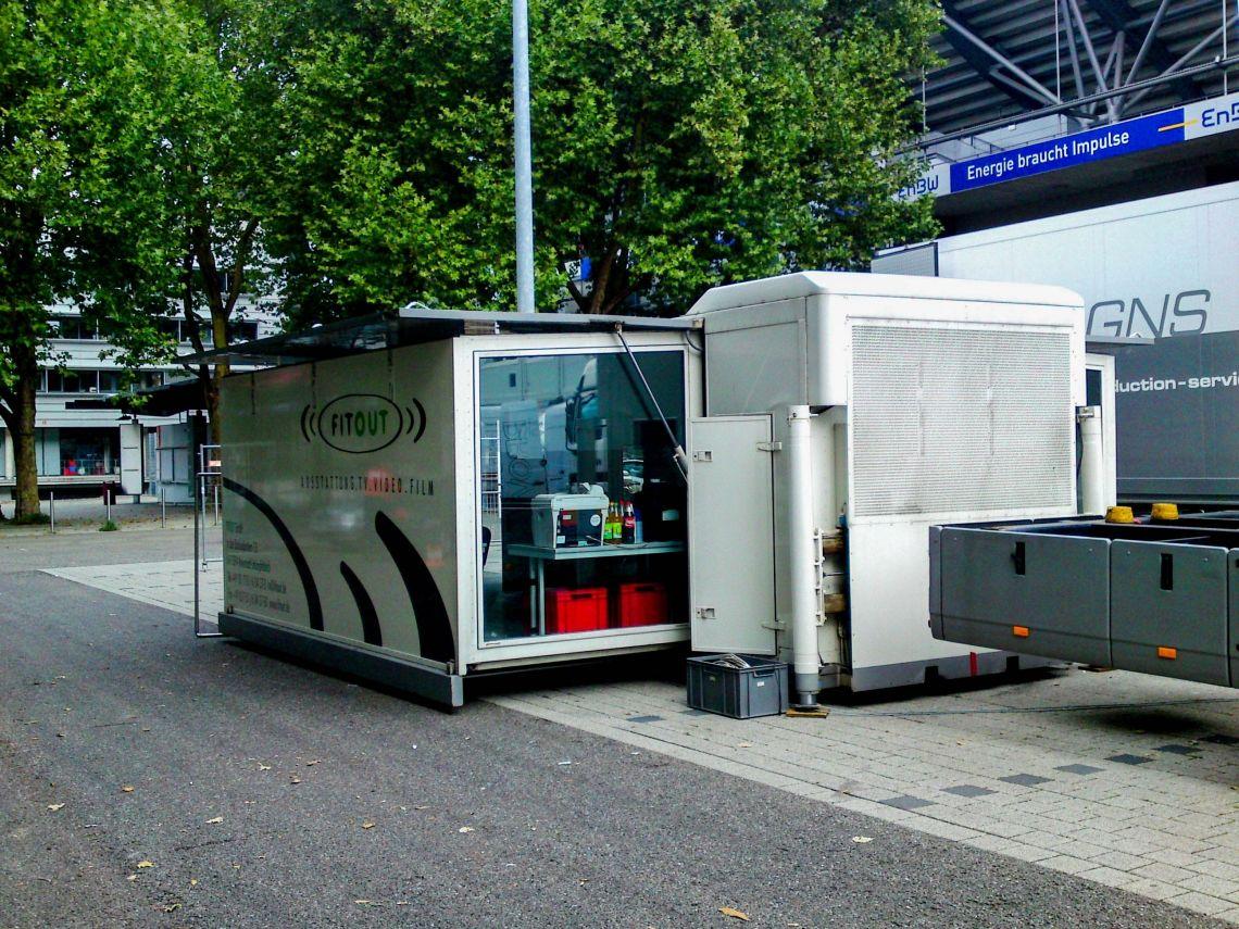 Mo6 - Produktionsmobil Das Mo 6 ist ein selbstfahrendes Trägerfahrzeug, welches mit einem abnehmbaren Wechselcontainer mit sich führt. Der Container wird durch vier hydraulische Stützen mittels Bedienpult auf dem Boden positioniert. Alternativ kann der Container auch auf dem Trägerfahrzeug belassen werden. Durch eine Außentreppe ist der Innenraum somit begehbar.  Der Container besitzt zwei ausschiebbare Schubladen, welche den Innenraum auf ca. 35 m² erweitern. Der große Büroraum ist in zwei Bereiche geteilt, welche jeweils durch eine abschließbare Türe getrennt werden können. Das herausnehmen der Innenwand ist natürlich auch möglich um somit einen einzigen Raum zur Verfügung zu stellen. Durch die vier großen Seitenfenster ist der Raum sehr lichtintensiv gehalten.