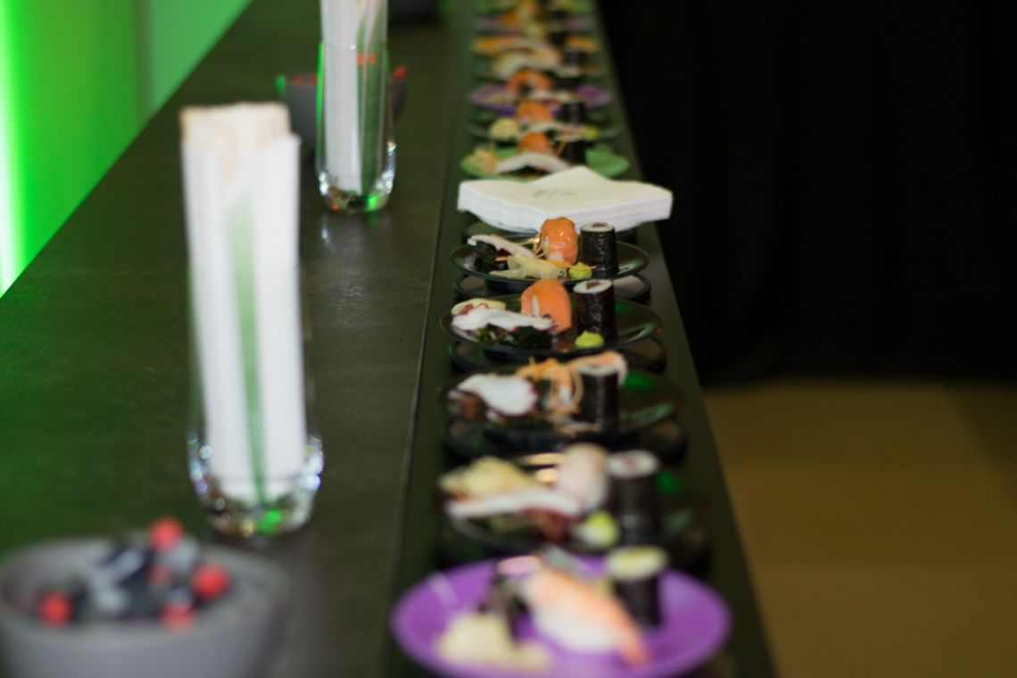 Sushibar mit Förderband   Pre-Motion Auf das Förderband stellt die Bedienung im Handumdrehen die Sushis, Cocktails oder andere Leckerbissen. Der Gast guckt sich die Augen aus dem Kopf nach all den Leckereien, die vorbeikommen.