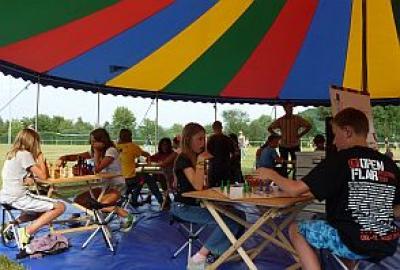 Das Brettspielzelt mit den Spieltischen von innen Auf schicken Klapphockern sitzen die Spieler an den Spieltischen aus Birkenholz. Auf den Tischen liegen die Brettspiele und Gesellschaftsspiele, wie zum Beispiel Malefiz, Halma, Schach, Mühle, Dame, Mensch-Ärgere-Dich-Nicht, Ludo, Mikado, Domino, Backgammon, Kulami, Bango, Six, Sedici und viele Spiele mehr. Die Spiele sind für Kinder und Erwachsene oder die ganze Familie geeignet. Das große Zelt mit den Brettspielen ist ideal für Festivals, Parkfeste, Familientage, Tage der offenen Tür, Stadtfeste.