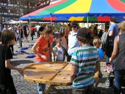 """Das große Hattrick vor dem Zelt von Spiel-o-Top in Esslingen Auf dem Hafenmarkt der Stadt Esslingen findet jährlich zweimal im Frühjahr und im Herbst ein großes Spieleparadies für Kinder und Erwachsene statt. Es steht meistens ein großes buntes Zelt, das so genannte """"Zirkuszelt"""" und mehrere kleine vierfarbige Zelte auf dem Platz. In und um die Zelte sind die Holzspiele und Großspiele aufgebaut. Hier finden Kinder, Eltern und Großeltern die Spiele Jakkolo, Carrom, Hattrick, Weykick, Murmelaufzug, Holzkreisel in der Kreiselkiste, Kreativwerkstätten wie Basteltische, Speckstein, Filzen, Staffeleimalen, Traumgärtchen oder Windlichter basteln. Auch die Brettspiele im großen Zelt standen schon auf dem Hafenmarkt in Esslingen. Mit Halma, Schach, Mühle, Dame, Ludo, Mensch-Ärgere-Dich-Nicht, Domino, Mikado, Kulami, Six, Bango, Sedici und vielen anderen Gesellschaftsspielen."""