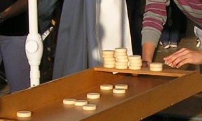 Spielsteine beim Jakkolo-Spiel Dies ist ein Detail des beliebtesten Spieles der Holzspiele von Spiel-o-Top. Es ist das Jakkolo-Spiel, ein traditionelles Spiel, das in den Niederlanden unter dem Namen Sjoelbak bekannt ist. Es wird mit 30 Holzscheiben gespielt. Der Spieler lässt die Scheiben in Richtung der vier Fächer am Ende des langen Spielbrettes aus Holz rutschen. Er versucht die Spielsteine auf dem Jakkolo möglichst gleichmäßig zu verteilen, denn nur so bekommt er möglichst viele Punkte. Das Sjoelbak ist eines von vielen Holzspielen oder Großspielen von Spiel-o-Top, die bei den Spielpaketen Familienspiele I, Familienspiele II oder Familinenspiele XL mit dabei sind. Die Spiele stehen in und um die bunten runden Zelte von Spiel-o-Top.