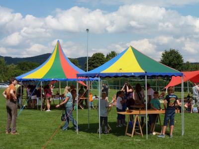 Zwei Zelte mit Holzspielen von Spiel-o-Top Auch hier wieder die Familienspiele mit den Holzspielen oder Großspielen von Spiel-o-Top: Jakkolo, Carrom, Weykick, Hattrick und Labyrinth. Sie stehen unter dem bunten 6m-Zelt und unter dem kleinen 4m-Zelt. Im Hintergrund die 3000 Bauklötze auf Teppichboden unter einem roten Sonnensegel. Die ganze Spielinstallation steht auf dem Rasenplatz auf dem Open Flair Rockfestival in Eschwege mit täglich 20.000 Besuchern.
