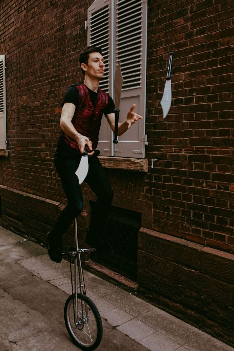 Ein Jongleur packt aus (Show) Mit Messern auf dem Hocheinrad jonglierend